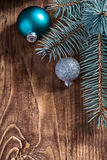 Blue and silver christmas balls and pinetree branch on old woode Royalty Free Stock Photography