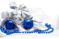 Blue and silver Christmas balls with silver bows  on white satin Stock Images