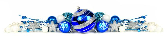 Blue and silver Christmas ornament border over white. Christmas border of blue and silver ornaments and branches isolated on a white background royalty free stock image