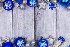 Blue and silver Christmas ornament double border on white wood. Blue and silver Christmas ornament double border with snow frame on a rustic white wood Stock Photo
