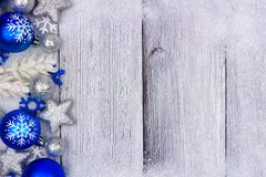 Blue and silver Christmas ornament side border on white wood. Blue and silver Christmas ornament side border with snow frame on a rustic white wood background Royalty Free Stock Photography