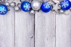 Blue and silver Christmas ornament top border on white wood. Blue and silver Christmas ornament top border on a rustic white wood background royalty free stock photos