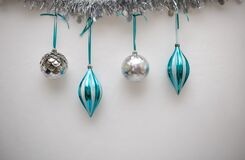 Blue and Silver Christmas Ornaments hanging with a White Background