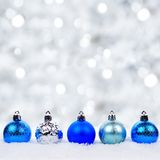 Blue and silver Christmas ornaments in snow with twinkling background. Blue and silver Christmas ornaments in snow with twinkling silver background stock photos