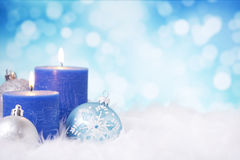 Blue and silver Christmas scene with baubles and candles. Blue and silver Christmas baubles and candles on a soft feathery surface in front of defocused blue and royalty free stock photo