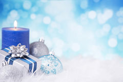Blue and silver Christmas scene with baubles. Blue and silver Christmas baubles, a gift and a candle on a soft feathery surface in front of defocused blue and Royalty Free Stock Photos