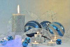 Blue and Silver Holiday. Candles with blue and silver  ribbon blue and silver  ball ornaments. Horizontal Stock Photos