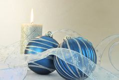 Blue and Silver Holiday. One large silver candle with 2 blue and silver balls and silver ribbon on creamy background. Close up. Horizontal Royalty Free Stock Photos