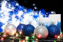 Blue and silvery christmas balls, a glowing garland and two non-burning candles on the background of a festive firework Royalty Free Stock Images