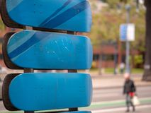 Blue skateboard decks horizontally hanging on rail with people w. Some blue skateboard decks horizontally hanging on rail with people walking in background Royalty Free Stock Photos