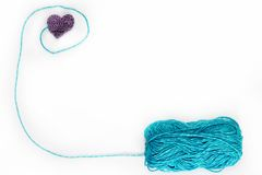Blue skein with crochet heart. White background Stock Photos