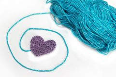 Blue skein with crochet heart. White background Stock Image