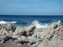 Blue skies and blue coastals. Waves smashing in rocks and blue skies Stock Photo