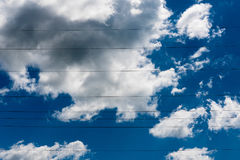 Blue skies with clouds and electrical cables across it stock photo