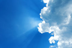 Blue skies with clouds and sunbeams Royalty Free Stock Image
