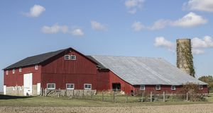 Blue skies and clouds surrounding a barn. A beautiful farm scene under cover of a blue sky and clouds on a beautiful autumn day stock photo