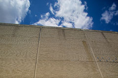 Blue skies over grey wall Royalty Free Stock Photography