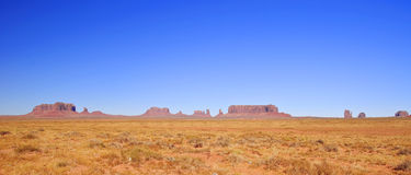 Blue skies over Monument Valley in Utah Stock Images