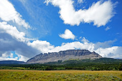 Blue skies over a mountaintop in Glacier. Stock Photo
