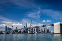 Blue skies over the San Francisco skyline and the bay bridge crossing in front of the Salesforce Tower. Bright blue skies with wispy clouds over the San stock image