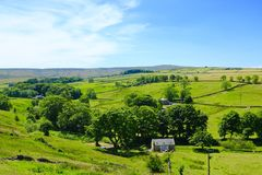 Blue skies over Weardale. Looking south over Weardale with lush green meadow land and trees under blue skies and white whispers of cloud royalty free stock image