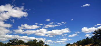 Blue skies, partly cloudy Stock Images