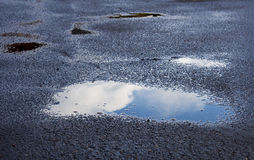 Blue Skies in Rain Puddle. The reflection of blue skies in a rain puddle stock image