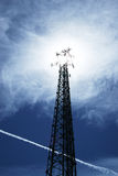 Blue skies and tall orders. A communications tower rises in the afternoon sky.  The clouds radiate like the radio waves being transmitted across the land Stock Images