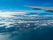 Blue skies with white clouds. Blue skies and white clouds over coastline as seen from the airplane flying over royalty free stock photography