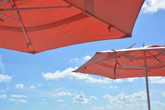 Blue Skies, White Clouds, and Umbrellas. Peach/orange coloured umbrellas against blue skies with fluffy white clouds. Perfect day. Island life royalty free stock photo