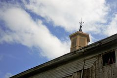 Wooden Cupola on old barn with weathervane on top. Blue skies white wispy clouds sunny new wood siding summer time stock photography