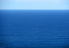 Blue sky. Meets deeper blue water stock photography