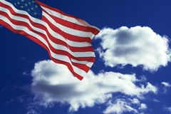 Blue sky. Flag against blue sky with dramatic white clouds royalty free stock photography