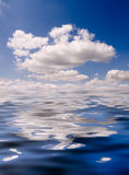 Blue Sky. Bright Blue Sky and Puffy White Clouds Reflected in Water Stock Images