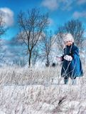 Blue sky. Picture of a 2 year old playing in the snow during a sunny day Stock Photos