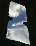 Blue Sky. View through the dark window of an ancient ruin to the blue sky and white clouds beyond royalty free stock image
