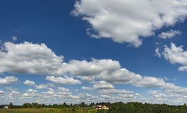 Blue sky. High clouds on high sky. Small houses near horizont Royalty Free Stock Photography