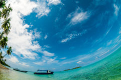 Blue sky above a boat at the seashore. Tropical island photographed with fisheye lens Stock Photography