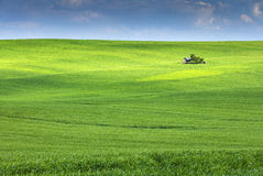 Blue sky above green field with shadows and little farmhouse Royalty Free Stock Images