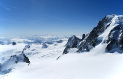 Blue sky above peak and clouds, the Alps. Clear blue sky above peaks stretching to the skyline and white clouds, black rock among snow field in the foreground Stock Photos