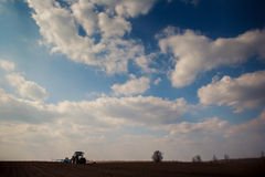 Blue sky above ploughed field tractor single tree on skyline Royalty Free Stock Photo