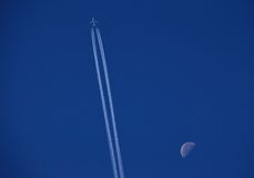 Blue sky, airplane and waning moon Royalty Free Stock Photos