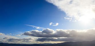 Blue sky background with scattered clouds over mountains silhouette. Aerial, panoramic photo banner Royalty Free Stock Photo