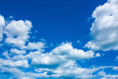 Blue sky background with clouds in bright sunny summer day. Royalty Free Stock Images