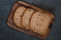 Blue sky background. On a cutting board sliced bread on a concrete background Stock Image
