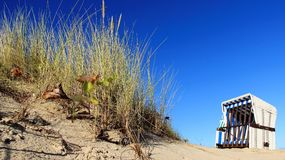 Blue Sky Background  And One Local Beach Chair. One topical beach chair with colorful grass grove and clear blue sky. sunny days in Germany Stock Photo