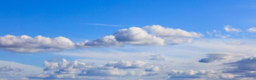 Blue sky background with scattered colorful clouds. Aerial panoramic photo. Space for text, banner. Royalty Free Stock Photography