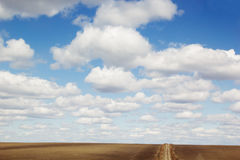 Blue sky background with soft silky clouds, strip field and road. Royalty Free Stock Images