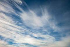 Blue sky background with tiny stratus cirrus striped clouds. Clearing day and Good windy weather.  royalty free stock image