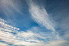 Blue sky background with tiny stratus cirrus striped clouds. Clearing day and Good windy weather stock photo
